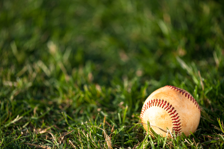 Close up of used worn baseball on grass field