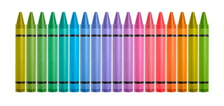 Rainbow colored crayons lined up on white background Фото со стока