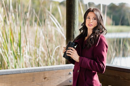 birdwatcher: Young woman on wooden nature trail with binoculars in early autumn Stock Photo