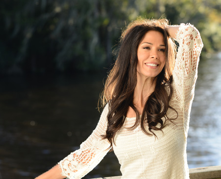 casually dressed: Casually dressed brunette relaxes next to river Stock Photo
