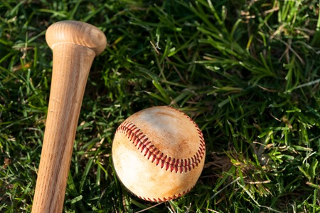 Close up of baseball and bat on grass