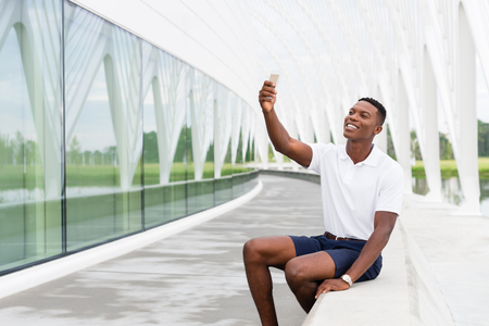 Black, African American college student smiling and taking a selfie with mobile phone on university campus Zdjęcie Seryjne - 44848542