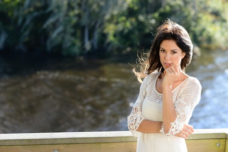 casually: Casually dressed brunette pensive next to river