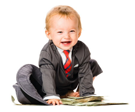 One year old baby girl sitting on US twenty dollar bills in business suit isolated on white background