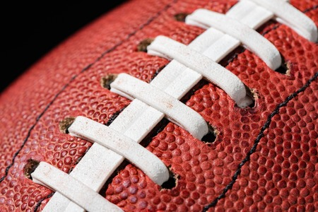 extreme close up: American football extreme close up on laces against black background Stock Photo