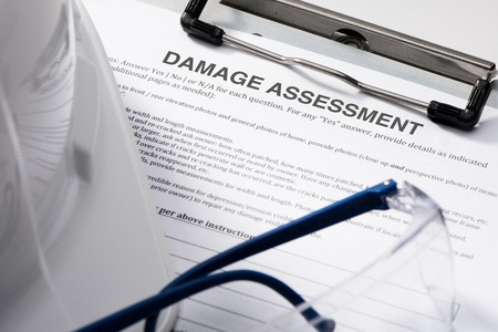Damage assessment form with safety glasses and hardhat on clipboard
