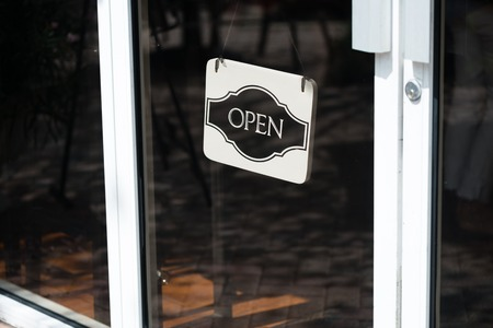 Black and White open sign hanging in store glass door