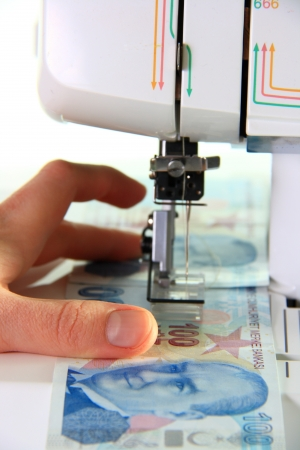 sewing machine sewing money turkish lira on white background photo