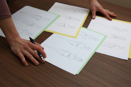 design studio: designer assessing fashion drawings on the collection of clothes Stock Photo