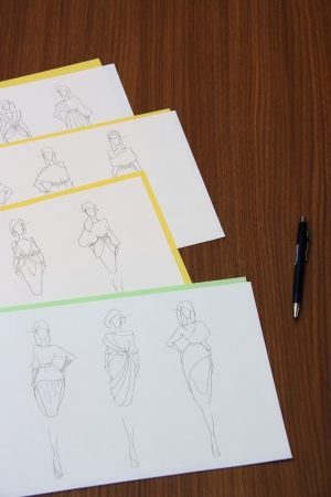 editors: designer assessing fashion drawings on the collection of clothes Stock Photo