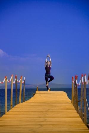 peer to peer: hermosa mujer en el ejercicio cerca del mar en pares de madera