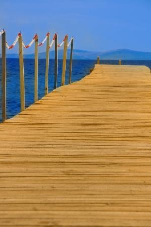 peer to peer: pares de madera en el mar azul con el cielo azul
