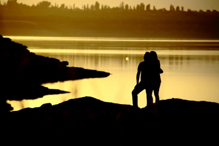 romantic couple watching sunset while standing photo