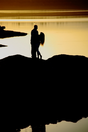 romantic couple dancing near lake at sunset time photo