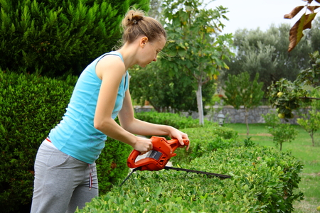 Girl pruning shrub in garden with electrical pruning tool