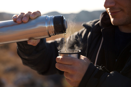 Campers drinking hot tea and coffeo from  bottle