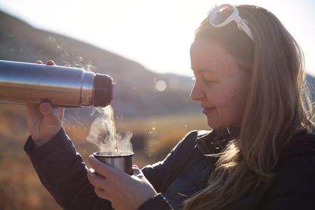 Campeggiatori che bevono tè caldo e caffè dalla bottiglia