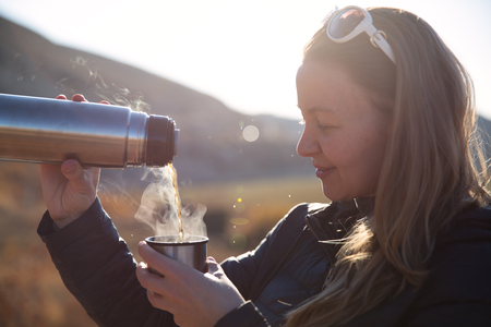 Camper trinken heißen Tee und Kaffee aus der Flasche