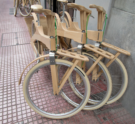 front wheel wooden bicycle near the grey wall