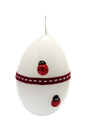 white candle with ladybug in the from of eggs isolated white background