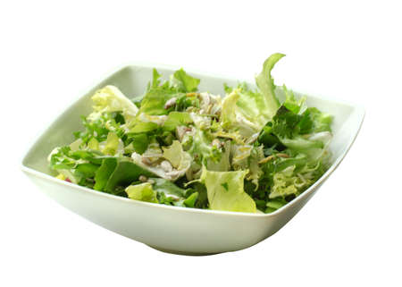 nice greens salad with nuts and sesame seeds on a white plate