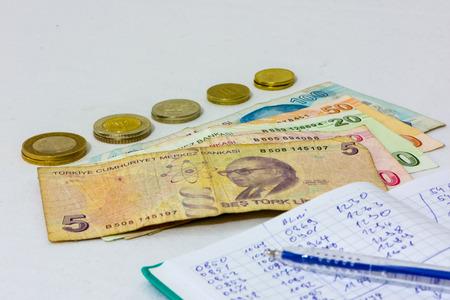 Hacer un informe del dinero gastado y escribirlo en el cuaderno Foto de archivo - 92058810