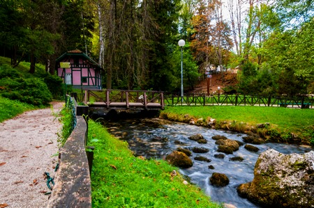 Smal house next to the river Bosna at beautiful park Vrelo Bosne Stock Photo