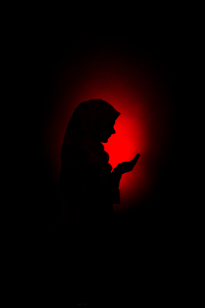 silhouette of a muslim woman praying to Allah