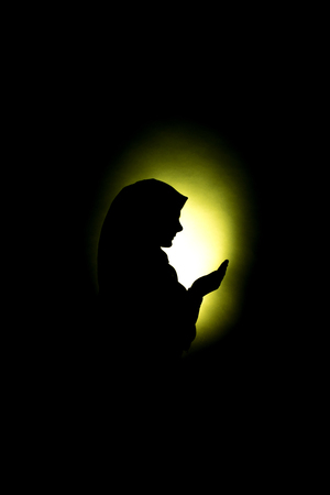 silhouette of a Muslim woman praying