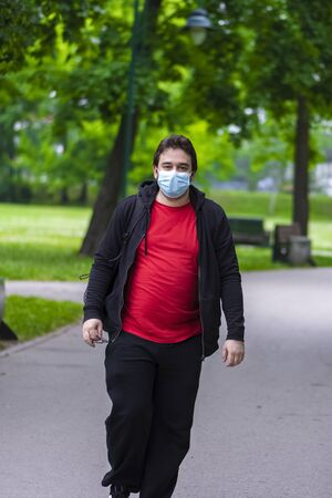 Man follow measures and wearing face mask against corona virus while he is walking in the park