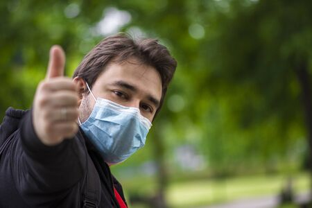 Man wearing surgical face mask following measures against corona virus pandemic showing ok sign, thumb up, finger up staying positive in new lifestyle with corona