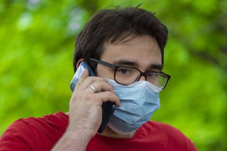 Man wearing surgical face mask during corona time talking on the mobile phone