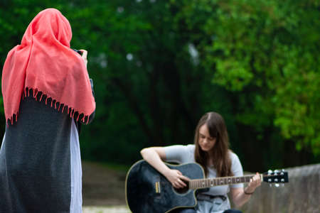Muslim girl taking photo by professional camera of young girl while playing guitar outdoor. Friends, sisters, together in nature