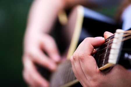 Closeup shot of girl's hand playing acoustic guitar outdoor.