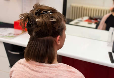 Beautiful teen girl at the hairdresser blow drying her hair after cutting it