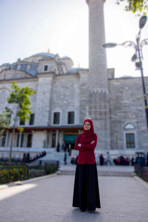 Muslim tourist girl posing in front of ancient Fatih mosque in Istanbul city, visit and travel to best destination in Turkey, summer tourism