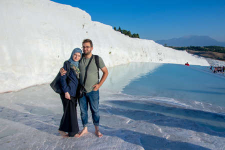 Happy muslim couple at the Pamukkale attraction. Tourist at honey moon visit and travel famous turkish destination. Love tourism in turkey