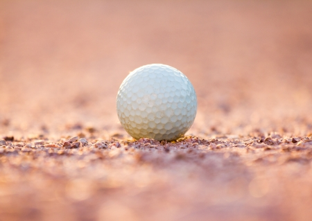 Golf ball on the sand in the evening  photo