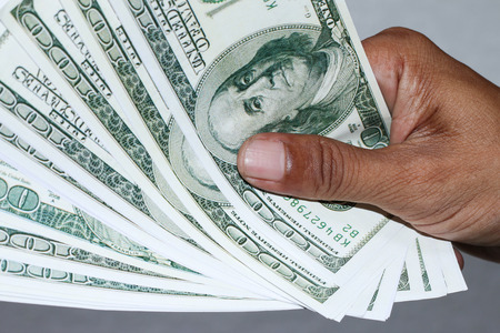over paying: hand with dollar banknotes background.