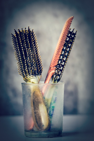 flaxen: Vintage hair combs old dirty in the dirty glass.
