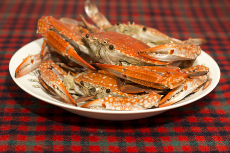 Boiled red crab on the plate on checkered tablecloths.