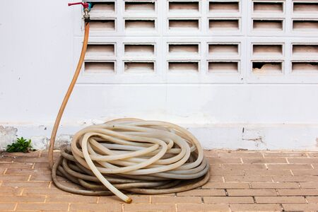 Old water hose on the floor background.