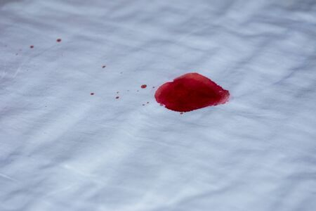 Drops of blood on a white cloth background. 스톡 콘텐츠