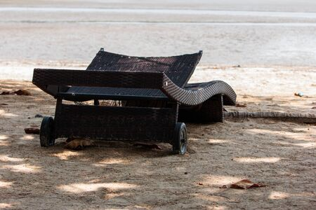 Old folding chairs under the shade of trees on the beach in the daytime of Thailand