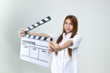 Young woman in action, holding clapperboard. Isolated over white background Stock Photo