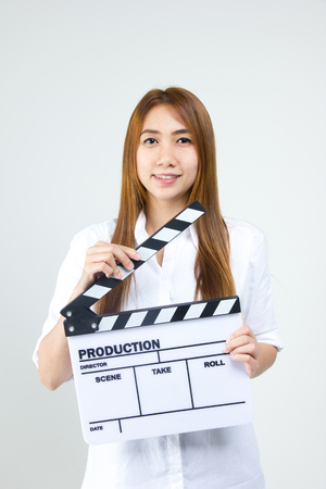 movie theater: Young woman in action, holding clapperboard. Isolated over white background Stock Photo