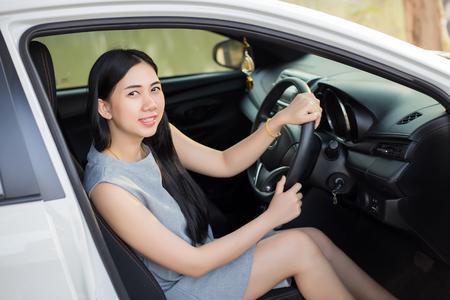 Pretty Asian women in a white car happy driving