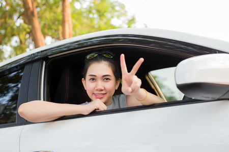 Woman drives a car and smiling