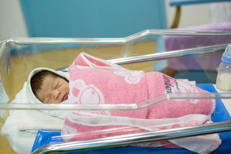 new born infant asleep in the blanket in delivery room Stock Photo