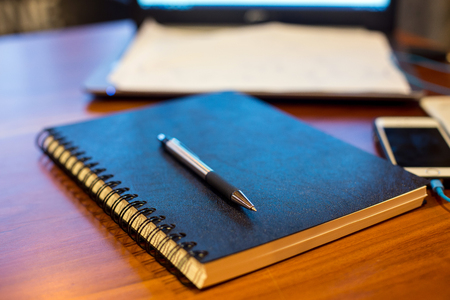notebook and pen on a wooden table Stock Photo